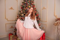 A bright girl in a sweater and a skirt is waiting for the New Year`s miracle. New Year`s themed shooting of the girl in anticipation of the New Year`s miracle Stock Photos