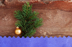 New Year's toy on a fir-tree branch on a wooden background. And blue carved paper Stock Images