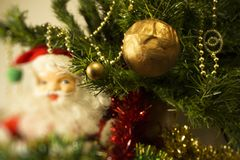 New Year`s toy golden ball on a Christmas tree in a festive tinsel with gold beads on a background of Santa Claus Stock Photography