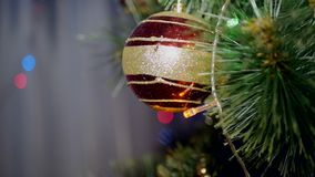 New year's toy swinging on a branch. Blinking garland on a Christmas. New Year's toy swinging on a branch. Beautiful Christmas ball with blinking stock video footage