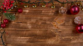 New Year`s toys lie on the table, garlands twinkle. Top view. New Year`s toys, decorative accessories lie on a wooden table and the lights of the garland twinkle stock video footage