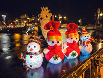 New Year`s toys snowmen and deer pose against night canals of Amsterdam. Royalty Free Stock Image