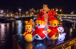 New Year`s toys snowmen and deer pose against night canals of Amsterdam. Stock Images