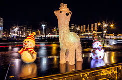 New Year`s toys snowmen and deer pose against night canals of Amsterdam. Royalty Free Stock Images