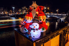 New Year`s toys snowmen and deer pose against night canals of Amsterdam.n Stock Photos