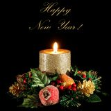 New Year`s wreath and a candle. Christmas card with a candle. Black background Stock Image