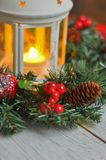 New Year`s wreath from a fir-tree on a white wooden background and a candle in a white candlestick. Stock Photography
