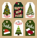 New Year Sale Tags with Trees and Decorations. New Year Sale cardboard tags with decorated trees, red hat, knitted sock and holly plant with thick sign vector Royalty Free Stock Images