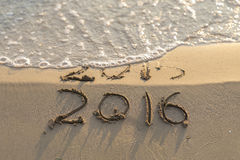 New year. Sea wave erasing 2015 on the shore Stock Photos