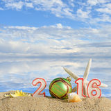 New year 2016 sign on a beach sand. With seashells, starfish and christmas ball royalty free stock photography