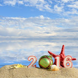 New year 2016 sign on a beach sand. With seashells, starfish and christmas ball Royalty Free Stock Images