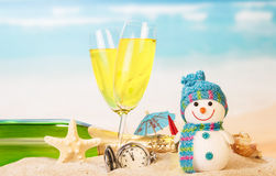 New year sign with champagne. Snowman on the beach background Royalty Free Stock Images
