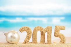 New year sign and christmas ball. New year 2015 sign and christmas ball on sandy beach Royalty Free Stock Images