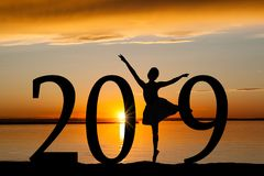 2019 New Year Silhouette of Ballet Girl at Golden Sunset. 2019 New Year silhouette of a girl dancing ballet at the beach during golden sunrise or sunset with Royalty Free Stock Image