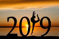 2019 New Year Silhouette of Girl Dancing at Golden Sunset. 2019 New Year silhouette of a girl dancing or exercising at the beach during golden sunrise or sunset Royalty Free Stock Images