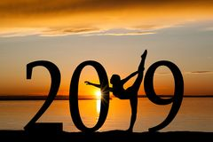 2019 New Year Silhouette of Girl Dancing at Golden Sunset. 2019 New Year silhouette of a girl dancing or exercising at the beach during golden sunrise or sunset Stock Photos