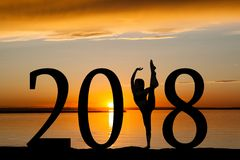 2018 New Year Silhouette of Girl Dancing at Golden Sunset. 2018 New Year silhouette of a girl dancing or exercising at the beach during golden sunrise or sunset Stock Photos