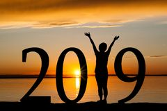 2019 New Year Silhouette of Woman at Golden Sunset. 2019 New Year silhouette of a girl with hands raised at the beach during golden sunrise or sunset with copy royalty free stock photos