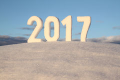 New year 2017 snow number. Numbers 2017 from snow crust on snowdrift against blue sky stock image