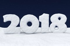 2018 New Year snow text on snow under night sky with stars. 2018 New Year sign text written with numbers made of snow on snowy field at night under cold north Royalty Free Stock Photo