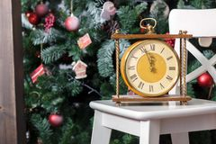 New year is soon. Retro clock on the white chair with the christmas tree on background. New year is soon. Retro clock on the white chair with the christmas tree stock image