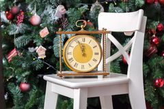 New year is soon. Retro clock on the white chair with the christmas tree on background. New year is soon. Retro clock on the white chair with the christmas tree royalty free stock photo