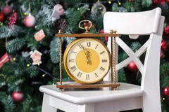 New year is soon. Retro clock on the white chair with the christmas tree on background. New year is soon. Retro clock on the white chair with the christmas tree royalty free stock photography