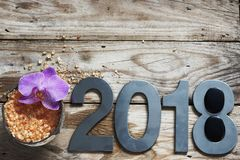 New Year 2018, spa set on wooden table, coconut and bath salt, flower of orchids and stones for hot massage royalty free stock images