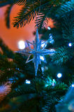 New Year star. New Year  toy on the new year tree with garland Stock Photo
