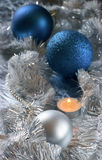 New-year still life. Blue and silver balls, candle and tinsel on silver background. Shalow DOF (edge of silver ball). Film scan Royalty Free Stock Photography