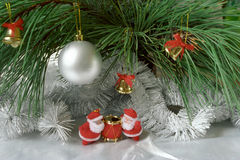 New-year still life. Two Santa Clauses on silver surface under green branches of conifer. Film scan Royalty Free Stock Photos