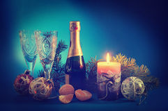 New Year still life with a candle and champagne Royalty Free Stock Images