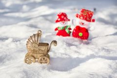 New Year stroller with a newborn on a background of a pair of happy snowmen. royalty free stock photo