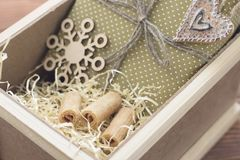 New year suprise in a box with a gift and cookies. New year surprise in a wooden box with a yellow filler. A handcrafted gold gift box with a thread, a Stock Photo