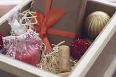 New year suprise in a box with a gift and cookies. New year surprise in a wooden box with a yellow filler. A handcrafted brown gift box with an orange ribbon. a Stock Images