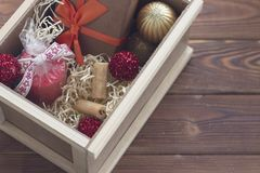 New year suprise in a box with a gift and cookies. New year surprise in a wooden box with a yellow filler. A handcrafted brown gift box with an orange ribbon. a Stock Image