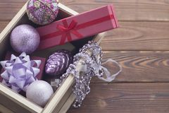 New year suprise in a box with a gift and ornaments. New year surprise in a wooden box. A red gift box with a red ribbon, a dark gift box with a lilac bow, lilac Royalty Free Stock Photography