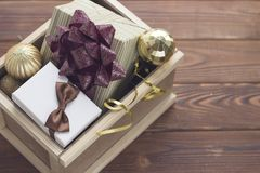 New year suprise in a box with a gift and ornaments. New year surprise in a wooden box. A white gift box with a brown satin bow, an olive green striped box with Royalty Free Stock Photography