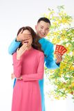 New Year suprise. Happy young men covering eyes of his girlfriend to give her lucky money envelops with best wishes inscription Stock Image