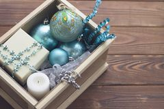 New year suprise in a box with a gift and ornaments. New year surprise in a wooden box. A beige gift box with a chain of blue star shaped beads, a white wax Stock Image