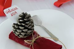 New year table decoration in minimal style, red napkin, dessert spoon and pine cone with greeting text `Welcome 2019`. New year table/plate decoration in minimal stock image