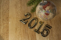 2015 New year text and Christmas Bauble. On the light wood Royalty Free Stock Photo