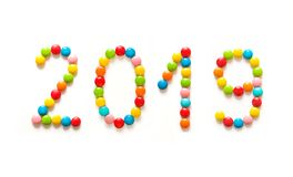 New Year 2019 text. Happy New Year 2019. Numbers 2019 made of multicolored sweet candy dragees on isolated white background. Creative composition of round Royalty Free Stock Photography