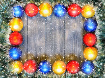New year theme: christmas decoration and balls on grey retro stylized wood background. With shiny snowfall Stock Image