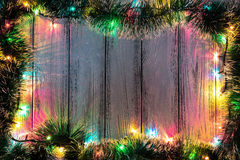 New year theme: christmas tree decoration and garland with colored lights on white stylized wood background Stock Images