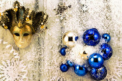 New year theme: Christmas tree white and silver decorations, blue balls, snow, snowflakes, serpentine and golden mask Royalty Free Stock Photography