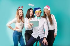 New Year theme Christmas winter office company employees. Group 4 young Caucasian people business smile holiday funny hats stock images