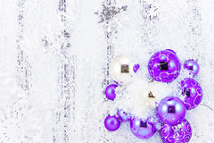 New year theme: purple and silver Christmas tree balls, snow, snowflakes, serpentine. On white retro stylized wood background black and white royalty free stock photos