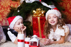 New year time. Happy childrens with cristmas presents near the fur-tree Royalty Free Stock Photos