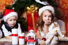 New year time. Happy childrens with cristmas presents near the fur-tree Stock Photography